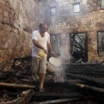 A man tries to put out smoke from his burnt house after clashes at Burj Abi Haidar street in Beirut
