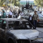 Residents walk past a burnt car as Lebanese soldiers secure the area at Burj Abi Haidar street in Beirut