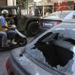 Residents ride a scooter past a car damaged during clashes at Burj Abi Haidar street in Beirut