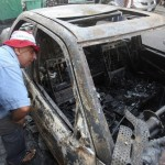 A man inspects a burnt car after clashes at Burj Abi Haidar street in Beirut